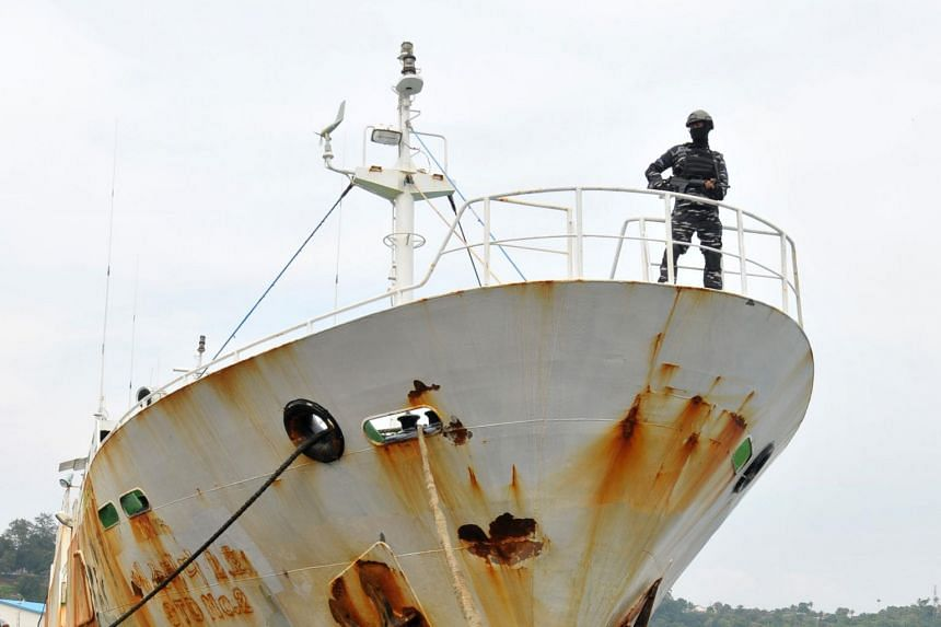 """A member of the Indonesian military (top) standing on a seized alleged """"slave ship"""" at the naval port of Sabang, on April 7, 2018."""