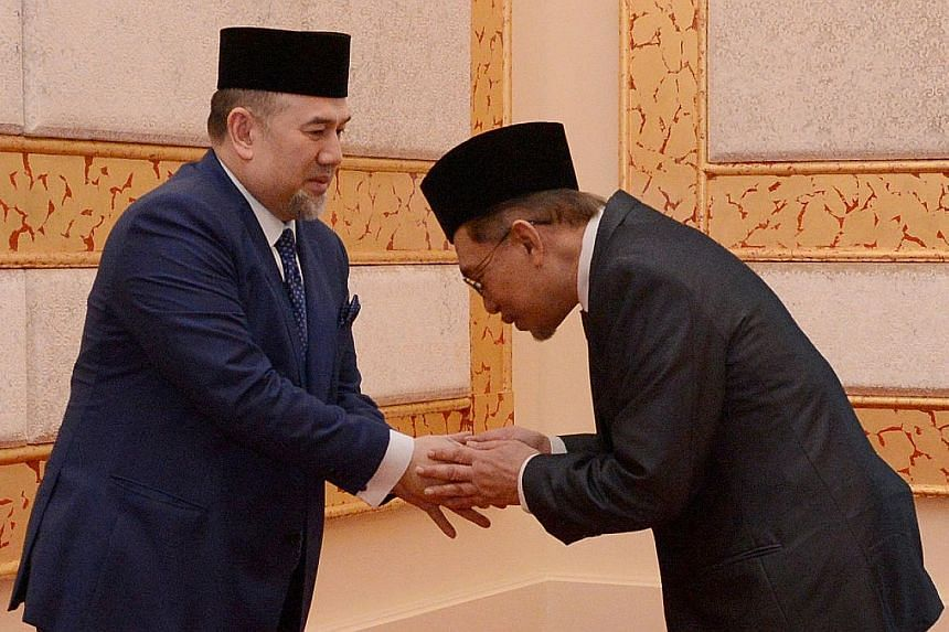 Mr Anwar Ibrahim meeting Malaysia's King, Sultan Muhammad V, at Istana Negara in Kuala Lumpur yesterday after receiving a royal pardon.