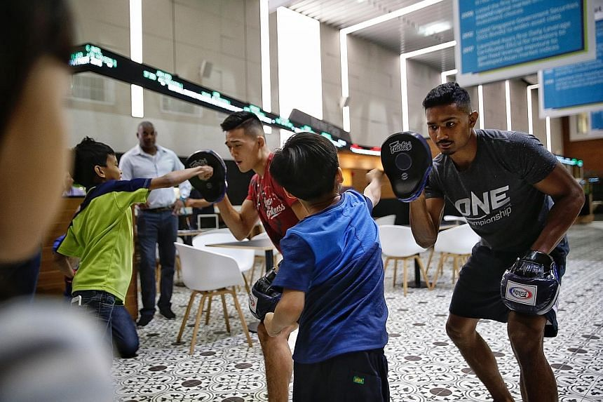 One Championship MMA exponents Christian Lee and Amir Khan giving underprivileged children from Fei Yue Centre a workshop on punching and kicking at the SGX Centre yesterday. SGX announced One Championship as the official fitness partner for this yea