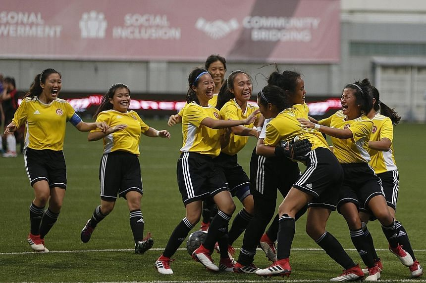Victoria JC players mobbing goalkeeper Insyirah Maritz after their 4-3 win on penalties against Hwa Chong Institution in the A Division girls' football final yesterday.
