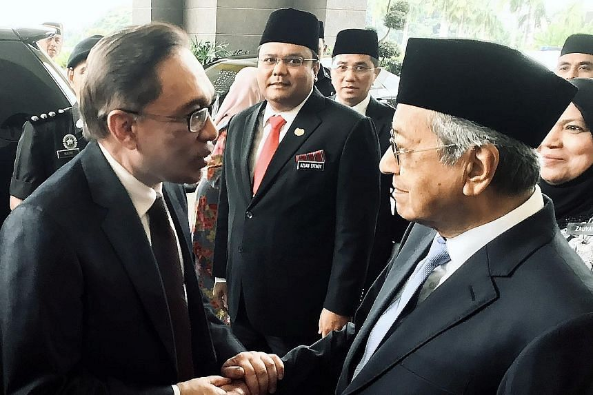 Freed Malaysian politician Anwar Ibrahim (left) being greeted by Prime Minister Mahathir Mohamad at Istana Negara in Kuala Lumpur yesterday. Datuk Seri Anwar had emerged earlier from a rehabilitation hospital in Cheras, where he was serving his sente