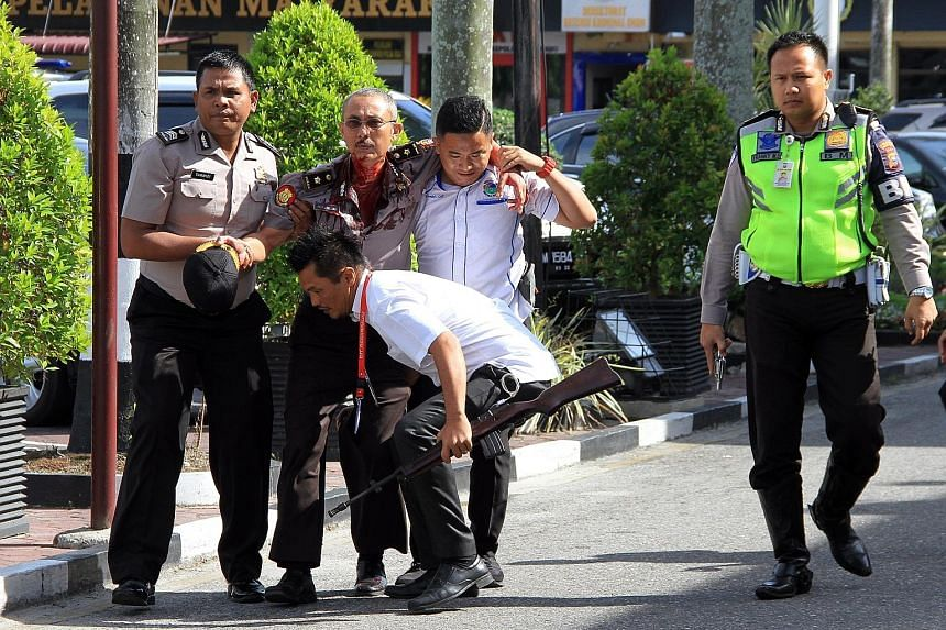 Top: An Indonesian police officer standing guard next to the body of a suspected attacker. Above: Indonesian police officers helping an injured colleague following the attack at the Pekanbaru police station by men using samurai swords. An Indonesian