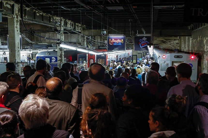 Commuters at Manhattan's Grand Central Terminal on Tuesday trying to get a train after a severe thunderstorm downed trees, causing power outages resulting in several lines being suspended.