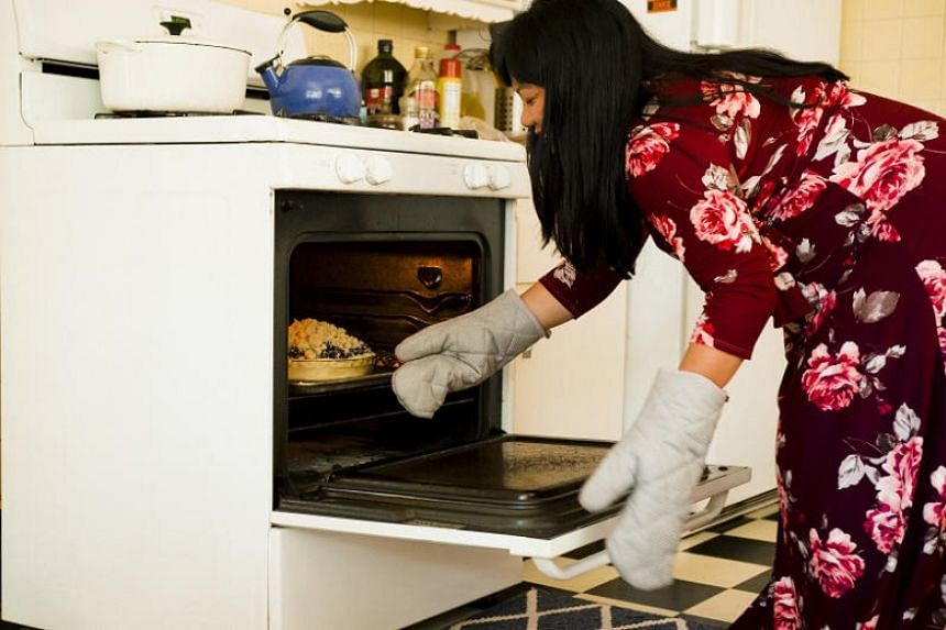 "Mia Hopkins, a romance novelist, baking a pie in Los Angeles on May 3, 2018. She has sometimes turned to procrastibaking — the practice of baking something unnecessary in order to avoid ""real"" work — as a way to overcome writer's block."
