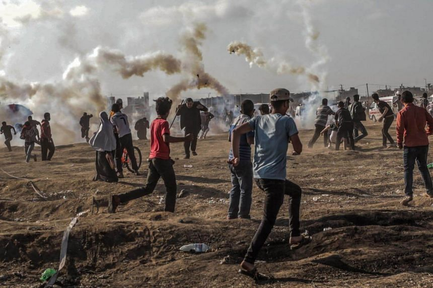 Palestinian protesters run for cover from Israeli tear-gas during clashes near the border on May 15, 2018.