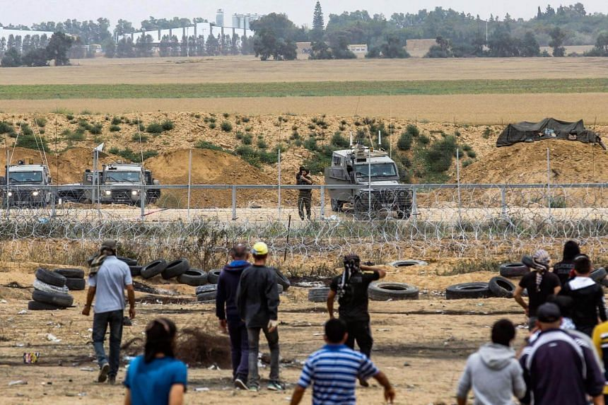 An Israeli soldier takes aim at Palestinian protesters from across the fence during clashes along the border on May 4, 2018.