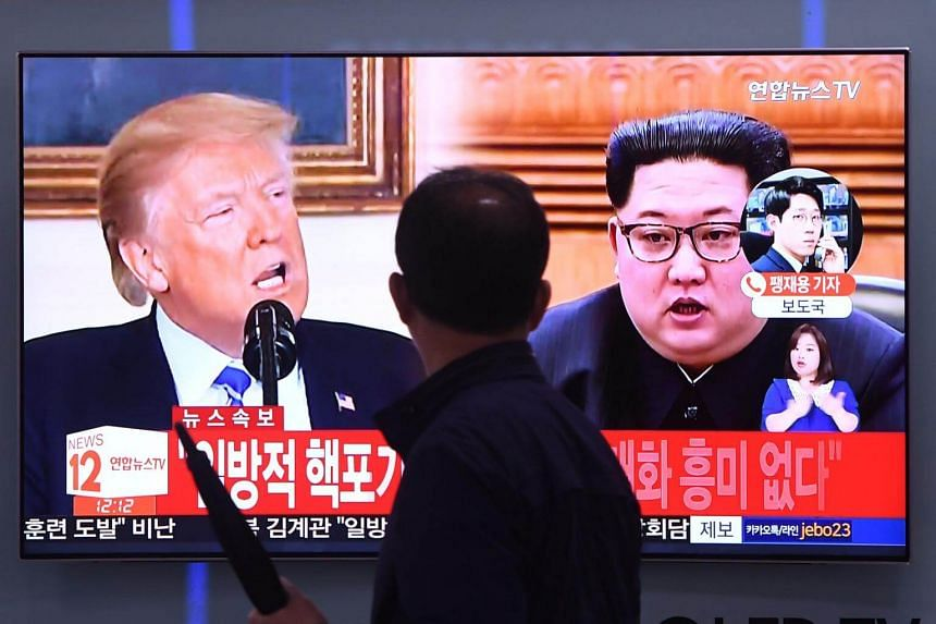 A man walks past a television news screen showing North Korean leader Kim Jong Un (right) and US President Donald Trump at a railway station in Seoul, on May 16, 2018.