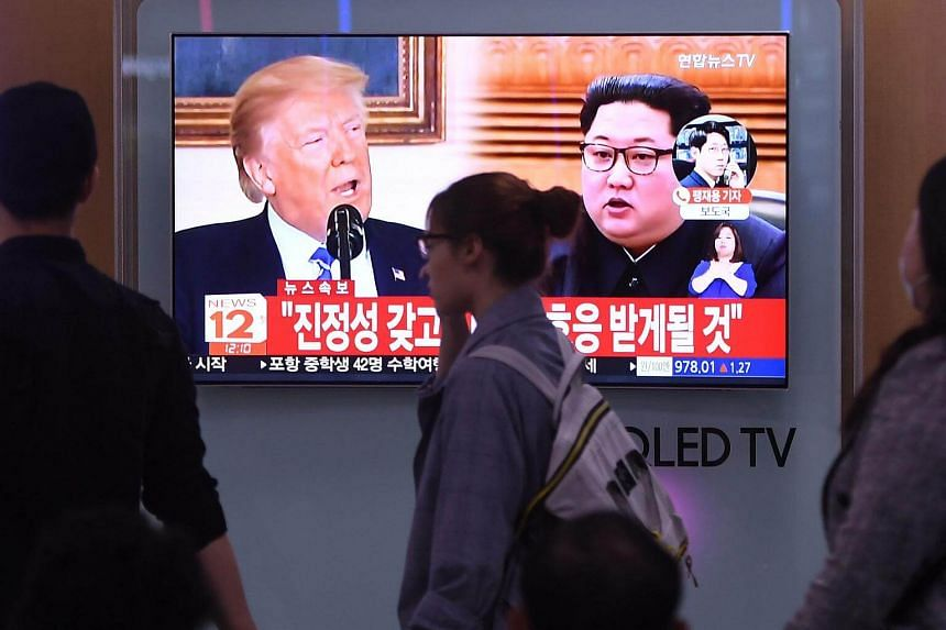 People walk past a television screen showing North Korean leader Kim Jong Un (right) and US President Donald Trump at a railway station in Seoul, on May 16, 2018.