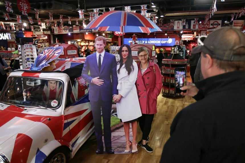 A woman poses for a photograph alongside memorabilia celebrating the forthcoming wedding of Britain's Prince Harry and his fiancee, US actress Meghan Markle.