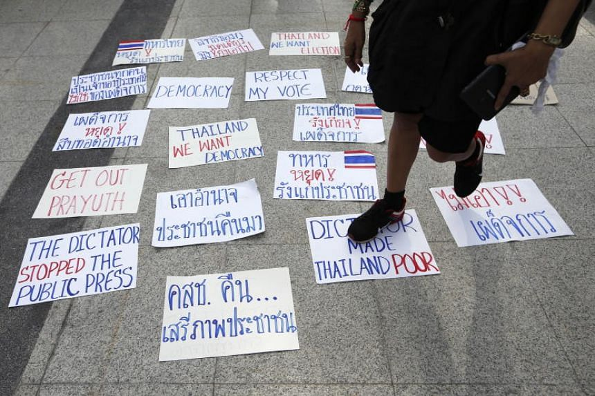 A Thai pro-democracy supporter steps on placards with anti-military junta slogans during a protest calling for a general election in Bangkok on May 5, 2018.