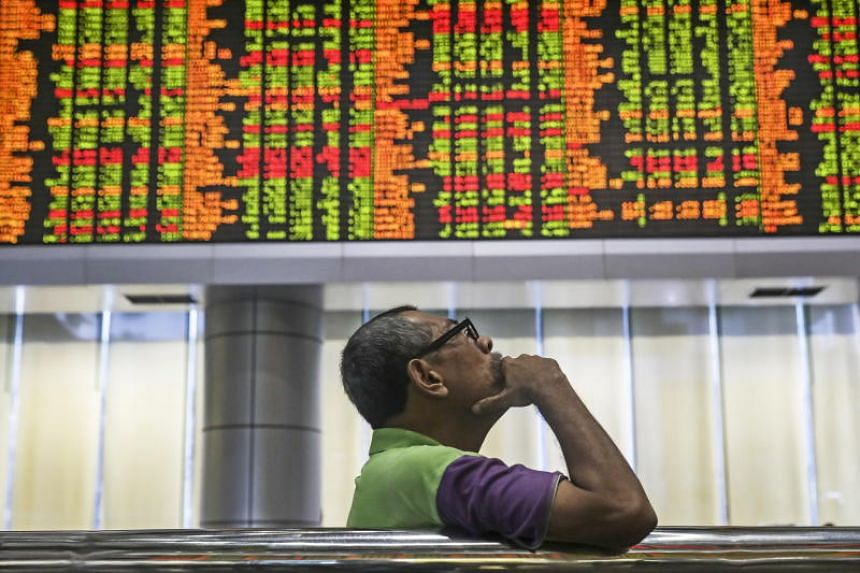 A man looks at trading boards at a private stock market gallery in Kuala Lumpur on May 14, 2018.