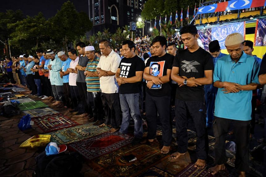 Supporters pray as they wait to listen to Malaysian politician Anwar Ibrahim's speach, during a rally in Kuala Lumpur, Malaysia on May 16, 2018.