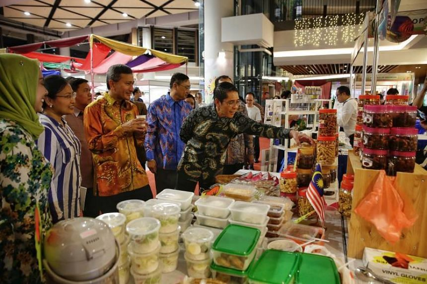 Foreign Minister Vivian Balakrishnan and Dr Maliki Osman stop at the Malaysian booth during a tour of the ASEAN Street Fair at Wisma Geylang Serai on May 17, 2018.