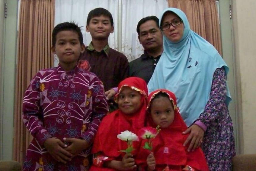 Indonesia's first female suicide bomber Puji Kuswati (in blue) with her family.