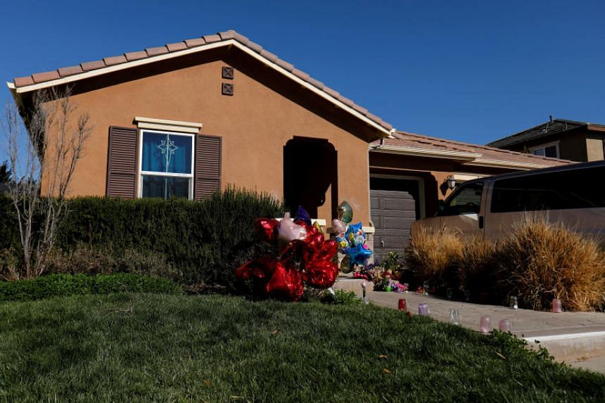 Balloons, stuffed animals and flowers are seen in the front yard of the home of David and Louise Turpin in Perris, California, on Jan 24, 2018.