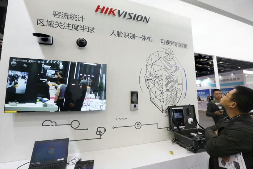 Visitors are seen at a booth of security camera supplier Hikvision Digital Technology during an expo at the National Convention Center in Beijing on March 12, 2018.
