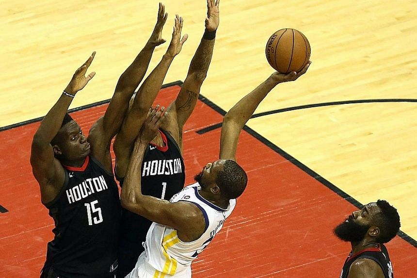 Golden State Warriors forward Kevin Durant (right), who had 38 points for the losing side, finds himself closely guarded by Houston Rockets centre Clint Capela (15) and forward Trevor Ariza during Game 2 of the Western Conference Finals in Houston.