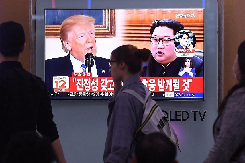 """A television news screen showing US President Donald Trump and North Korean leader Kim Jong Un at a railway station in Seoul. A South Korean presidential Blue House official said the South intends to more actively perform """"the role of a mediator"""" bet"""