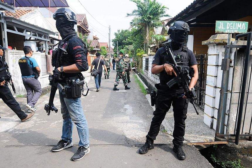 Officers from the anti-terrorism squad Densus 88 carrying out a raid in Tangerang in Java on Wednesday, following a spate of terror attacks in Indonesia.