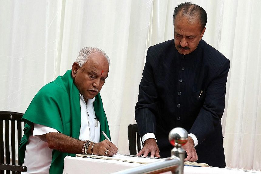 Mr B. S. Yeddyurappa signs the documents after he was sworn in as Chief Minister of Karnataka in Bangalore yesterday. The Congress party had tried to stop him from taking the oath.