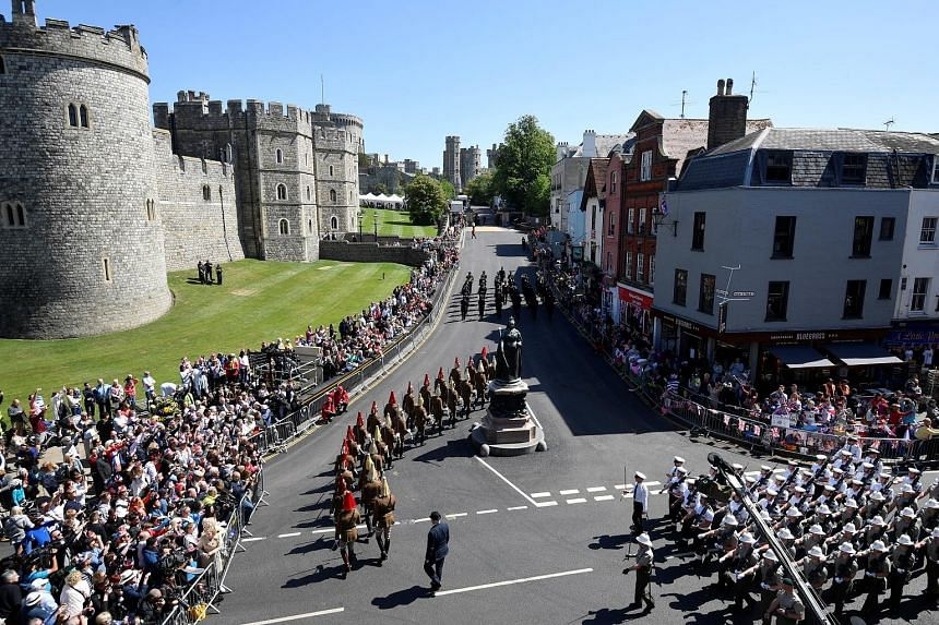 Police officers and members of the public watch as military personnel rehearse their part in the procession through the streets of Windsor for Prince Harry and Meghan Markle's wedding.