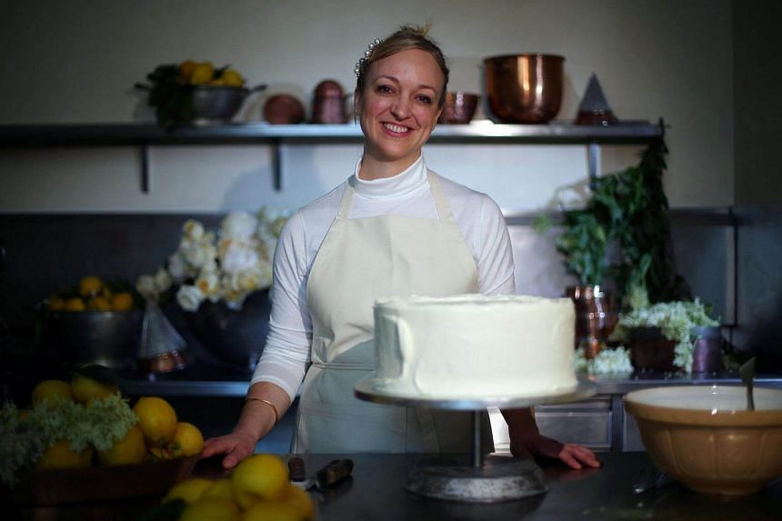 Owner of Violet Bakery Claire Ptak poses with a tier of the wedding cake of Britain's Prince Harry and US actress Meghan Markle in the kitchens of Buckingham Palace in London, on May 17, 2018.