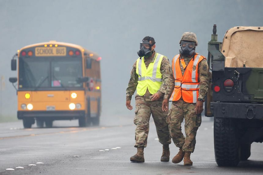 Hawaii National Guard soldiers wear masks to protect themselves from volcanic gases in Pahoa during ongoing eruptions of the Kilauea Volcano in Hawaii, US on May 17, 2018.