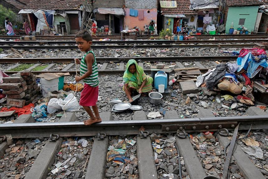 A boy walks past a woman cleaning her kitchen utensils between the railway tracks in a slum area of Kolkata, India.