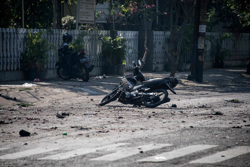 A damaged motorbike is seen at the scene outside a church following a suicide bomb in Surabaya, on May 13, 2018.