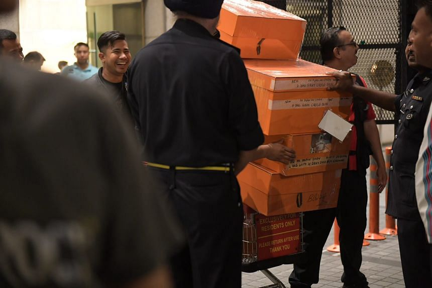A police truck being loaded with orange boxes, the signature colour of the French luxury brand Hermes, on May 18, 2018.