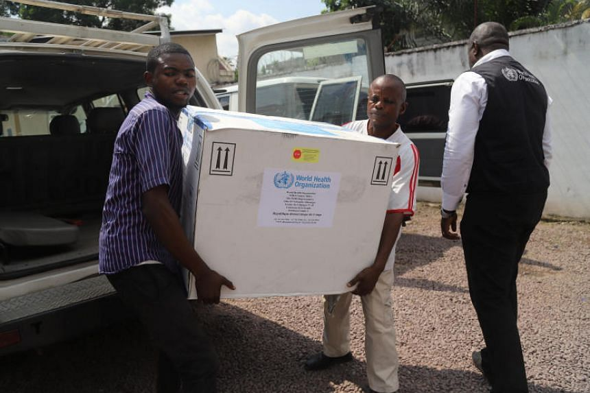 Congolese Health Ministry officials carry the first batch of experimental Ebola vaccines in Kinshasa, Democratic Republic of Congo, on May 16, 2018.