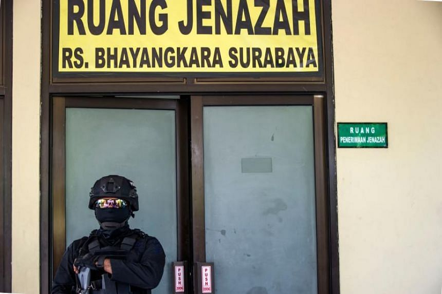 An anti-terror policeman keeps watch at a hospital morgue, where the bodies of the individuals involved in the Surabaya suicide bombings are being kept, on May 18, 2018.