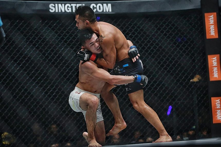 Right: Singapore's Amir Khan delivering a kick to South Korean Lee Sung Jong at last night's One Championship event at the Singapore Indoor Stadium. The 23-year-old Amir dominated the lightweight bout and won after the referee stopped the fight in th