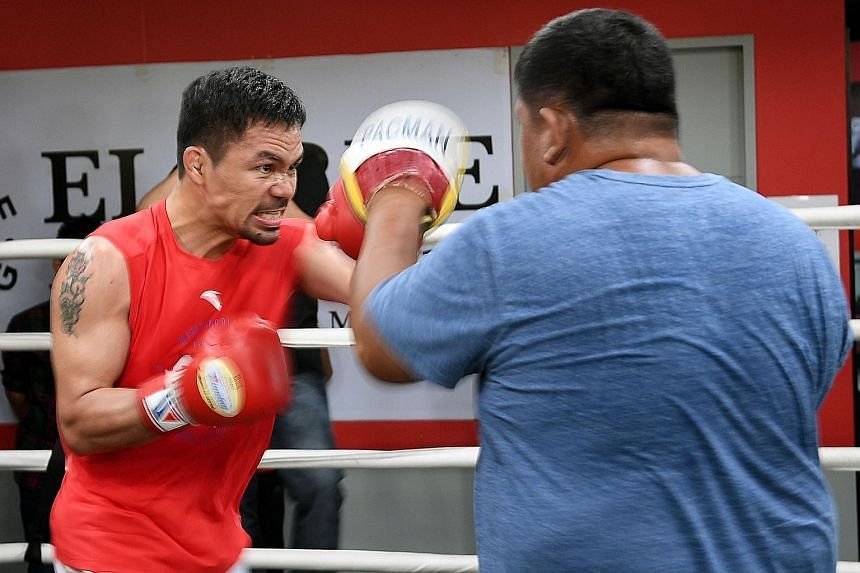 """Manny Pacquiao sparring with his childhood friend and assistant trainer Restituto """"Buboy"""" Fernandez during a training session in Manila on Thursday. Pacquiao is due to challenge Argentinian Lucas Matthysse for the WBA welterweight title on July 14."""
