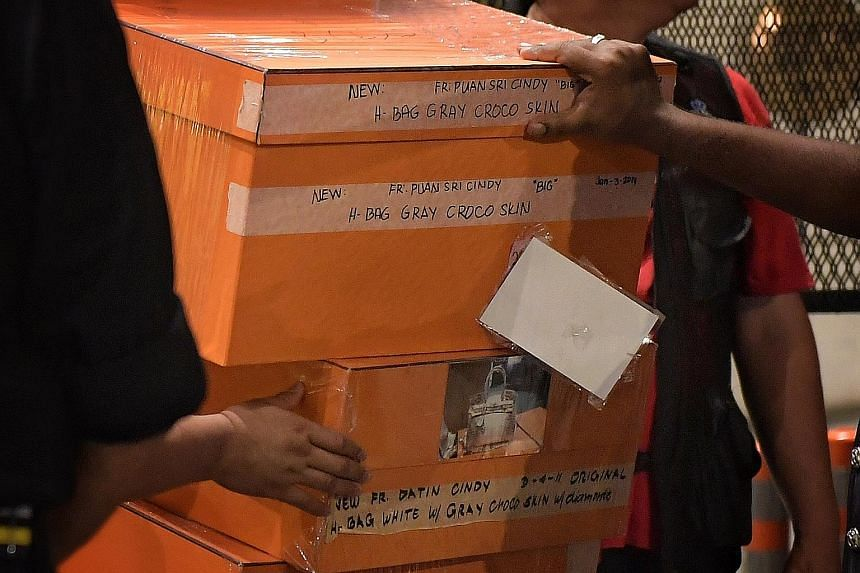 The police carted away bags filled with jewellery, cash, watches and other valuables, while many of the orange boxes were labelled with pictures and descriptions of different Hermes Birkin bags. Malaysian police removing items in a raid on Thursday n