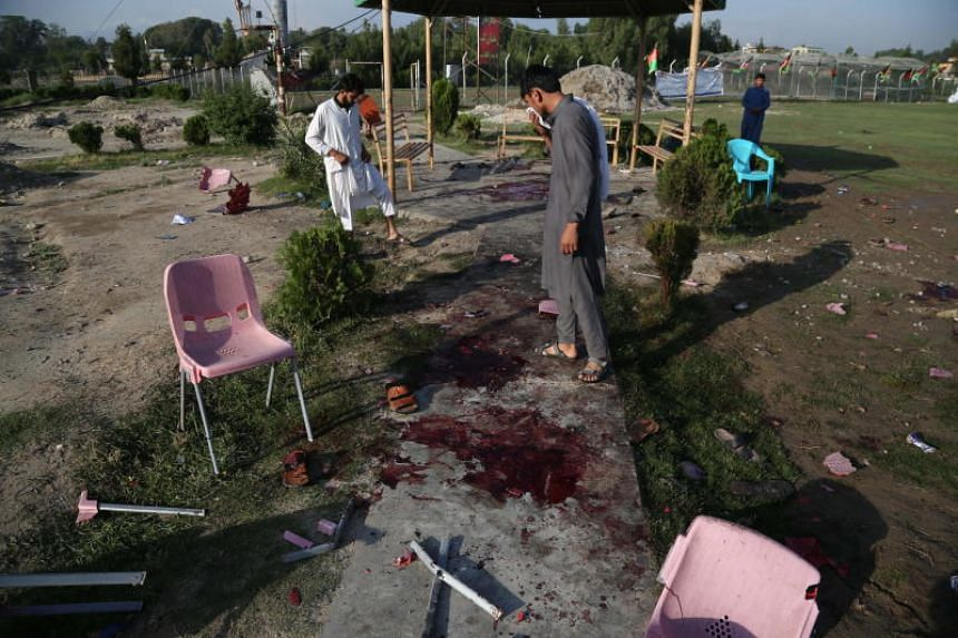 People survey the cricket ground where three bombs exploded in Jalalabad, Afghanistan, on May 19, 2018.