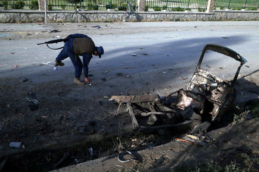 An Afghan security official inspects the scene of three bomb blasts at a cricket ground in Jalalabad on May 19, 2018.