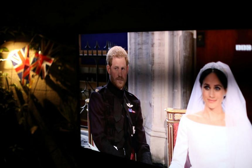A television screen sits next to Union Jacks during a royal wedding watching party for the wedding of Britain's Prince Harry and Meghan Markle in Hollywood, Los Angeles, California, on May 19, 2018.