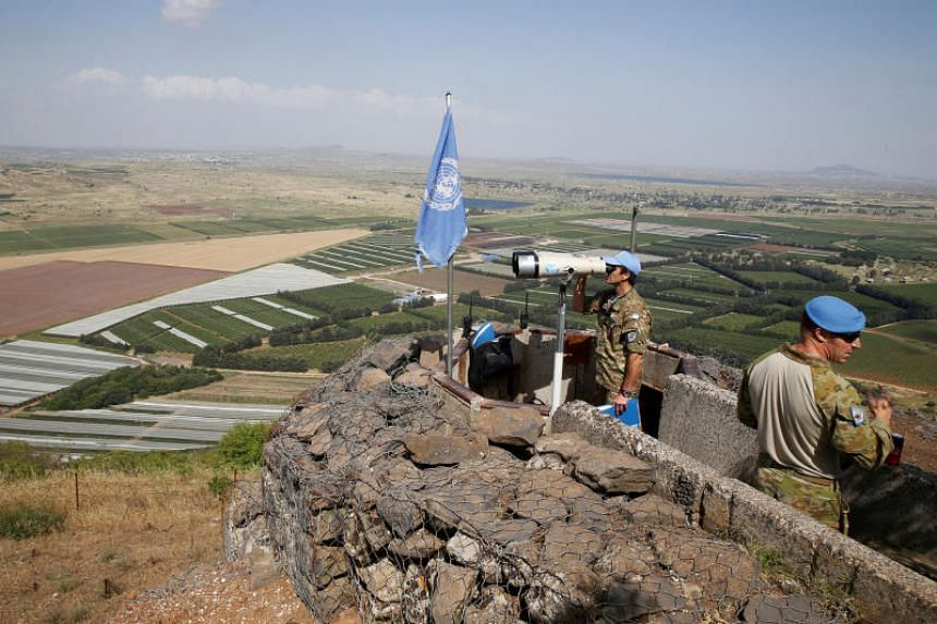 A United Nations Truce Supervision Organisation military observer uses binoculars near the border with Syria in the Israeli-occupied Golan Heights, Israel on May 11, 2018.