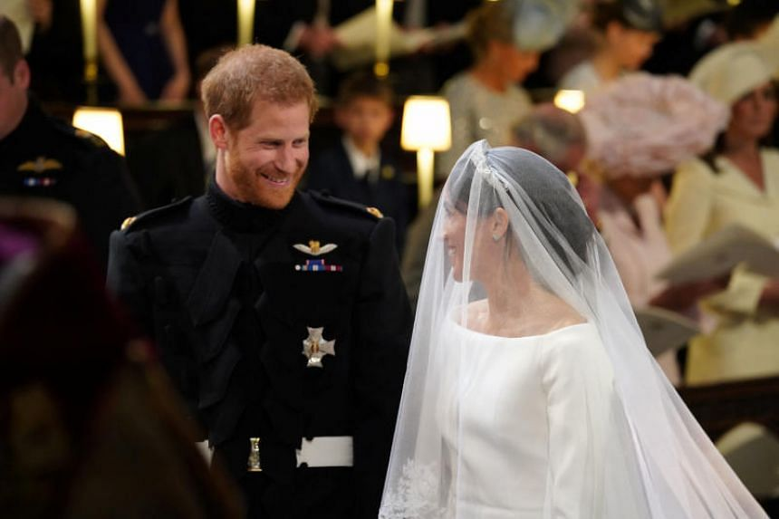 Prince Harry looks at his bride Meghan Markle as she arrives for their wedding in St George's Chapel at Windsor Castle on May 19, 2018.