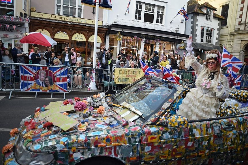A woman waves from an elaborately decorated car to Royal well-wishers preparing to bed down for the night on the High Street outside Windor Castle in Windsor on May 18, 2018, the eve of Britain's Prince Harry's royal wedding to US actress Meghan Mark
