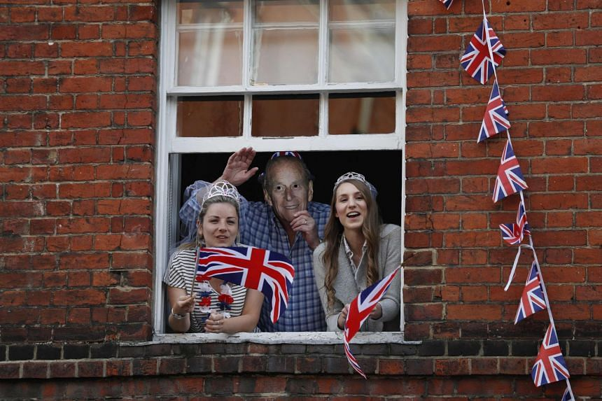 Royal fans lean out of windows as they watch Britain's Prince Harry and his best man Prince William, Duke of Cambridge, greet well-wishers on the street outside Windor Castle in Windsor on May 18, 2018, the eve of Prince Harry's royal wedding to US a