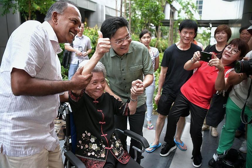 Above: Ministers K. Shanmugam and Lawrence Wong pose for a photo with Madam Su Ye Chu, 91, at the opening of Yishun Town Square yesterday. Left: Mr Lee Aik Lam conducts Lego art workshops for children and parents at a flexible workshop space at Block