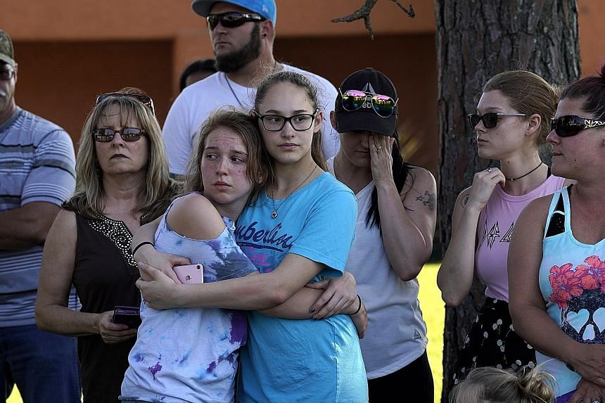 Those shocked by the shooting comforting each other at a vigil outside Santa Fe High School. The suspect, 17-year-old Dimitrios Pagourtzis (far left), surrendered and was taken into custody. He is being held on capital murder charges.