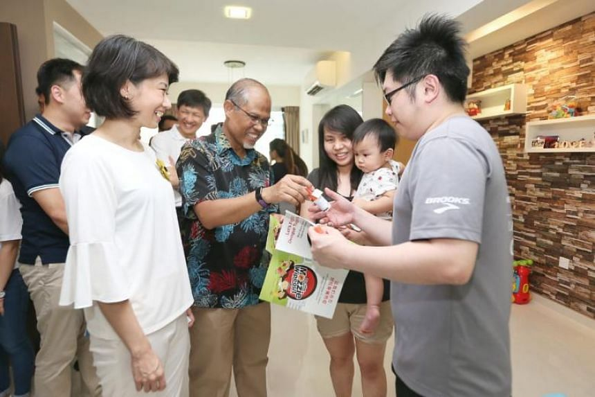 Residents receiving mosquito sprays and pamphlets at their home from Minister for the Environment and Water Resources Masagos Zulkifli (second left) and MP Sun Xueling (left) during the launch of the National Dengue Prevention Campaign on May 20, 201