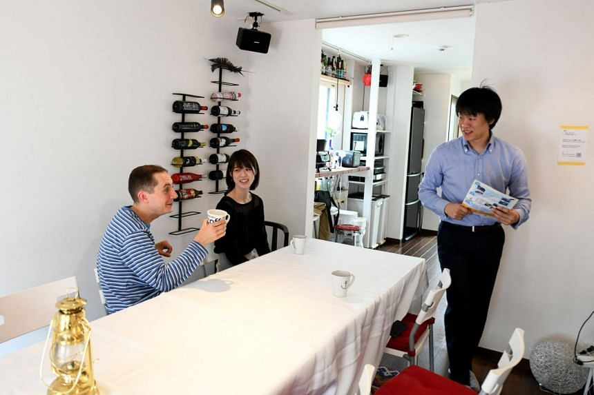 Room rental user Max Ikeda, a Ukrainian-Japanese living in Hiroshima (left), talking with rental house owner Nobuhide Kaneda (right) and his partner Hitomi Watanabe (centre) in Tokyo.