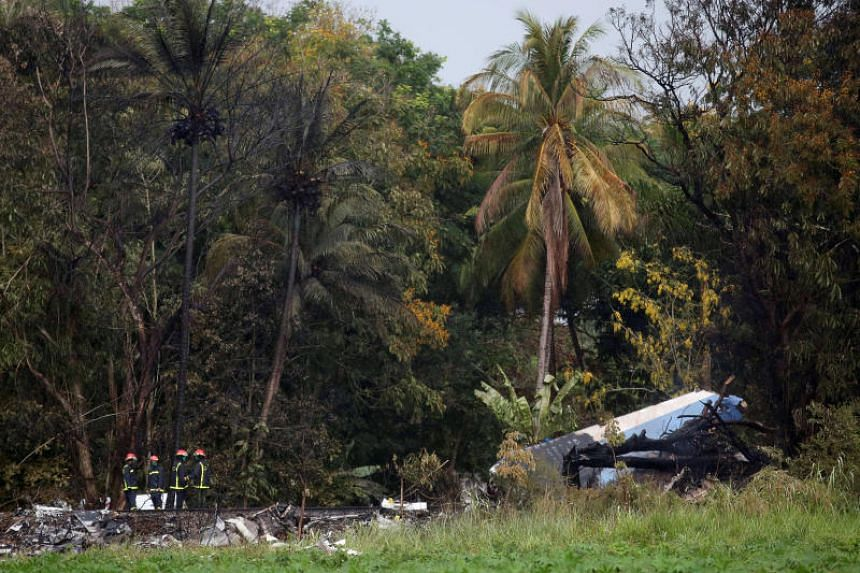 Firefighters work at the wreckage site of a Boeing 737 plane that crashed in the agricultural area of Boyeros shortly after taking off from Havana's main airport in Cuba, on May 18, 2018.