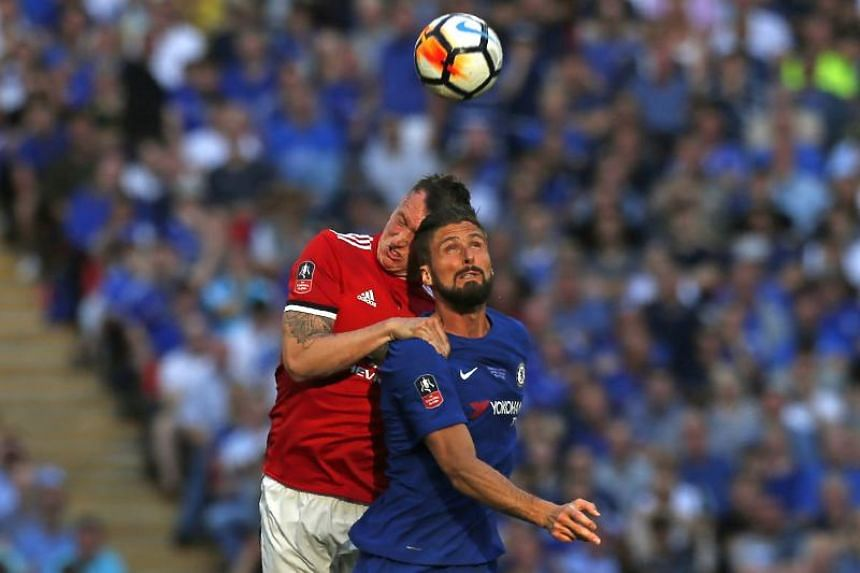 Manchester United's English defender Phil Jones (L) cuts his head in this clash of heads with Chelsea's French striker Olivier Giroud during the English FA Cup final football match between Chelsea and Manchester United at Wembley stadium in London on