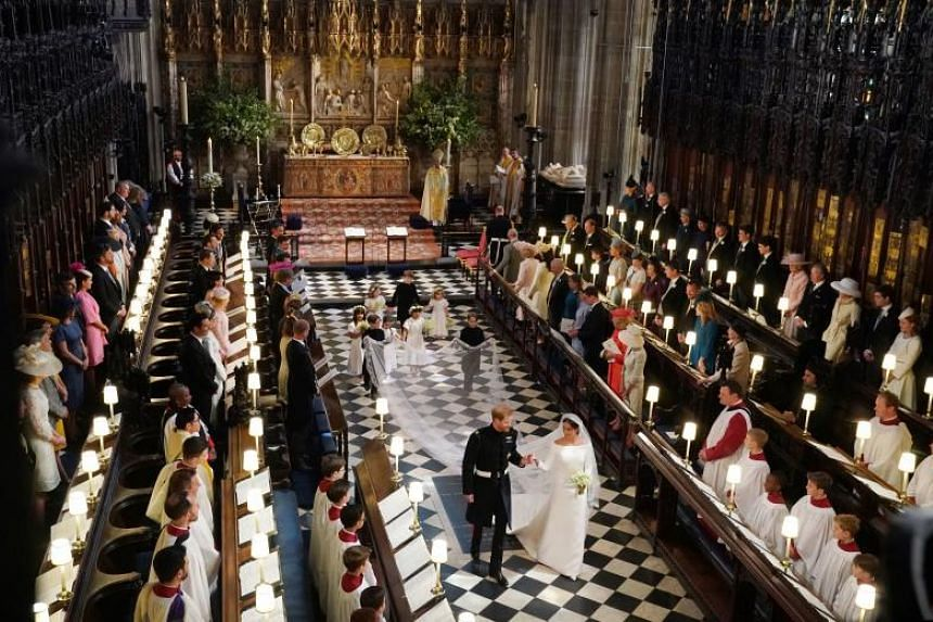 Britain's Prince Harry, Duke of Sussex and Britain's Meghan Markle, Duchess of Sussex, walk away from the High Altar toward the West Door to exit at the end of their wedding ceremony in St George's Chapel, Windsor Castle, in Windsor, on May 19, 2018.