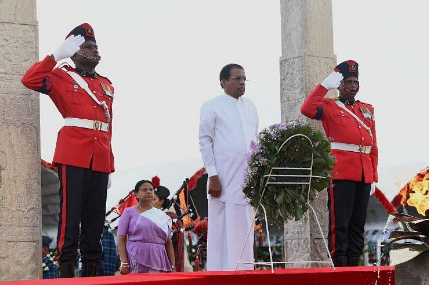 Sri Lankan President Maithripala Sirisena (centre) lays flowers at a memorial for those who died in the decades-long conflict against the Tamil Tigers, during a commemorative ceremony marking the 9th anniversary of the end of the islands Tamil separa